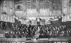 large orchestra and their conductor seen on the platform of Victorian concert hall in long shot