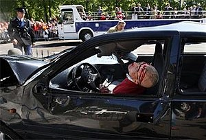 2009 attack on the Dutch royal family - The mortally injured Karst Tates still sitting in his car after the attack, with the royal bus in the background. This image by Pim Ras won an award as the best Dutch news photo of the year 2009.