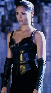 This image shows a black-haired woman with braided hair, wearing an all-black outfit with a corset top, pants and elbows-long handless gloves.