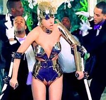 A woman wearing a metallic leotard and helmet is seen walking with a pair of crutches. Behind her, a number of dancers are visible, who are wearing tuxedos with white gloves, and making different gestures behind the woman.