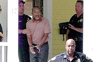 "On the porch of a yellow-clapboard house stands a middle-aged African American man in polo shirt and slacks, in the middle of a statement, his mouth agape, his hands handcuffed to the front. Behind him stands a uniformed Caucasian policeman, lightly grasping the man's upper arm. Facing the pair is an officer to the right, his left hand held up in a ""hold on"" gesture. Another African American officer is in the foreground, below the level of the porch, with his arms akimbo and his back to the scene while he faces the general direction of the camera."