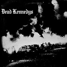 "A black-and-white photograph of a burning car outdoors at night. In the upper-left corner are the words ""Dead Kennedys"" in Gothic script."