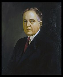 A color portrait of a man in his fifties wearing a suit