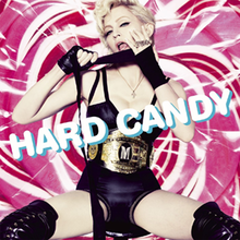 Madonna sitting in front of a pink background with her legs stretched. She is wearing a black leotard and a boxer belt, while pulling a black rope across her mouth with her hands.