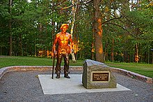 "Life-size bronze statue of a shirtless man with a hat, resting his right hand on a pick axe and holding a shirt in his left hand. The top half of the statue is lit orange by the setting sun. A boulder to the right has a plaque that reads ""Tioga County 'CCC Worker' 1933 - 1942""."