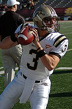 Football player in uniform appears to be getting ready to throw a football