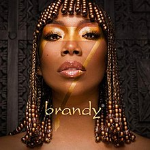 """A black woman stands in front of a carved wooden background. She wears her hair with micro braids and a number of golden beads that cover her fringe and the ends of her braids. Across her first is the number 7 in gold lettering and beneath is the word """"brandy""""."""