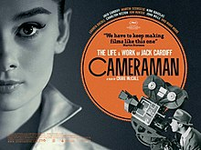 A movie poster dominated by a picture of Audrey Hepburn and a cameraman and his camera in the right hand bottom corner pointing up at her.