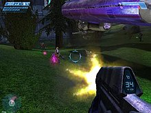 First-person view of the gameplay. In the lower-right corner of the screen, the player's weapon is shown as the player fires on small aliens in a lush outdoor environment. Indicators around the periphery of the screen display health and ammo count.
