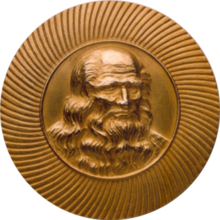 Obverse of a golden medal with the image of Leonardo da Vinci at the center facing slightly to the right.