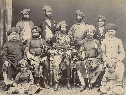 The Nawab of Junagadh Bahadur Khan III (seated centre in an ornate chair) shown in an 1885 photograph with state officials and family. Nawab junagadh1885.jpg