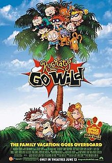 Several toddlers and a dog sit atop a palm tree, with a teenage girl, a younger girl a man, a young boy and a monkey standing underneath