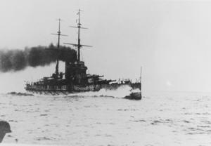 Een groot slagschip stoomt door het water.  Water breekt tegen de boeg terwijl zware donkere rook uit de twee trechters van het schip komt.