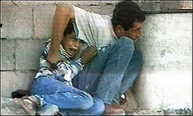A man with black hair wearing blue jeans and a white t-shirt crouches behind a wall and a white concrete cylinder. With his right hand, he is grasping the arm of a young boy, also with black hair, who is crouching on the ground behind him. The boy is wearing blue jeans, brown sandals, and a blue and white top. His right hand is holding onto the man's t-shirt. He looks as though he is crying. Behind them, the wall is made up of concrete blocks. The man's head is slightly down, and he is looking to his left.