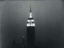 Grainy, black-and-white still frame of the illuminated Empire State Building against the night sky