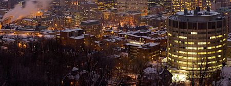 McGill's downtown campus at night viewed from Mount Royal. The circular building in the foreground is the McIntyre Medical Sciences Building.