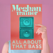 "A portrait of a woman posing in front of a pastel pink backdrop, wearing a light blue sleeveless top. She holds a picture that hides her face. On the picture is an image of two speakers. Above the speakers in green font stands the name, Meghan Trainor. Below it in the same font stands the title ""All About That Bass""."