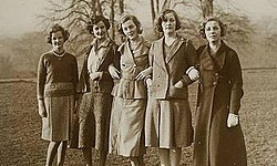Nearly full length group portrait of five well-dressed women standing in a field. Their ages range from roughly 20 to 30; their hair is cut short of the shoulders in elegant 1930s or 1940s styles; four of the five wear skirts down just below the knee, and one a longer coat. Two wear pearls.