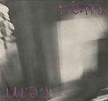 "A blurry black-and-white photo with ""r.e.m."" scrawled in purple in the top right corner and again upside down in the bottom left corner"