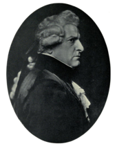Right profile of stern-faced man in dark clothing with lacy shirt and cuffs, wearing a wig