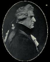 Правый профиль человека с суровым лицом в темной одежде, кружевной рубашке и манжетах, в парике.