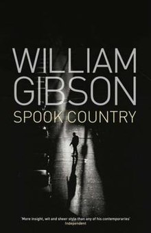 "A black-and-white photograph of a man crossing a dimly-lit street. Superimposed in block capitals on the upper half of the photograph is the text WILLIAM GIBSON, and below in smaller text, SPOOK COUNTRY, at the bottom of the image is a quote from the Independent: ""More insight, wit and sheer style than any of his contemporaries""."