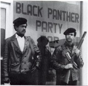 Black Panther Party - Black Panther Party founders Bobby Seale and Huey P. Newton standing in the street, armed with a Colt .45 and a shotgun.