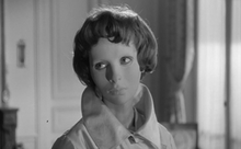Black and white screen capture of the film showing character Christiane wearing her white featureless mask that covers her face.