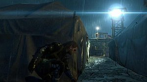 Metal Gear Solid V: Ground Zeroes - Snake avoiding a searchlight. Ground Zeroes introduces new visual aesthetics that allow players to recognize threats more easily, such as this lens flare.