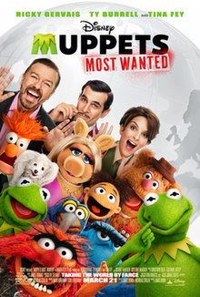 Group picture of the Muppets with two men and a woman standing behind them. In the background is a gray globe of the world.