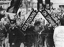 Image shows a parade through Central London, led by a banner reading 'Countdown on Spanner'