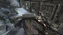 A brown-haired woman, the main protagonist, makes a leap from one ledge to another to reach a switch.