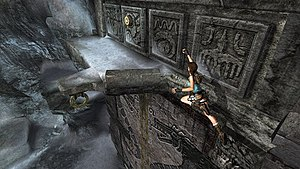 Tomb Raider - A gameplay screenshot from Tomb Raider: Anniversary, showing Lara jumping for a ledge below a door switch. While many mechanics within the Tomb Raider series have undergone changes, platforming and puzzle solving linked to this are recurring, standard elements within the series.