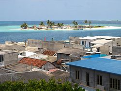 The island of Kandholhudhoo (foreground) that was completely destroyed by the tsunami of 2004. Residents took temporary residence in other nearby islands including Bandaveri island (background)