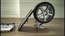 a flat board strikes the tread of a car tyre at a 45-degree angle. The tyre is balanced on top of a smaller piece of machinery on a wooden floor.
