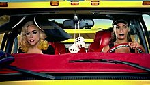 A blond woman sitting beside a brunette woman who is driving a yellow colored van. The blond woman wears a giant hat on her head. A pair of dice hangs from the rear-view mirror between them.