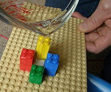 Water being poured over a Lego surface.