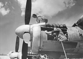 Men in overalls working on piston engines of military aeroplane