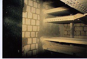 Passive fire protection - Fire-resistance rated wall assembly with fire door, cable tray penetration and intumescent cable coating.