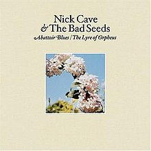 "A photograph of a series of flowers in part of an arc are surrounded by a cream coloured border. Black text above the photograph reads ""Nick Cave & The Bad Seeds"" and italicised black text reads ""Abattoir Blues/The Lyre of Orpheus""."