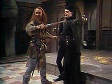 Dougal MacAngus, Duke of Argyll (Alex Norton) duels with Edmund, Duke of Edinburgh (Rowan Atkinson)