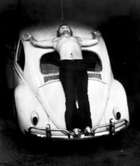 Chris Burden during the performance of his 1974 piece Trans-fixed where he was nailed to the back of a Volkswagen