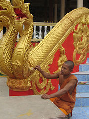 Monk repainting a naga (mythical dragon) at Pha That Luang