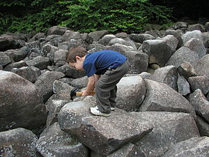 A child strikes a Ringing Rock
