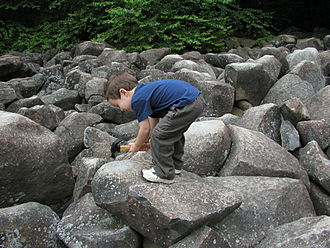 Ringing rocks - A child strikes a rock with a hammer at Ringing Rocks Park, Pennsylvania, to generate a distinctive bell sound.