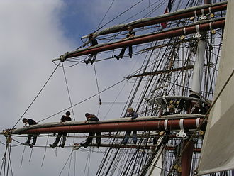 Yard (sailing) - The fore course is stowed neatly on top of its yard. On the Prince William this yard is made of steel, does not lift, and weighs around two tons. The two people higher up are working on the fore lower topsail yard. Here, the sails are bent only to the yards' quarters and the yardarms are very short.
