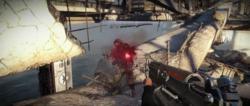 De first-person view van de speler karakter, bovenop een vernietigde brug, schieten een nazi met zijn machinegeweer.
