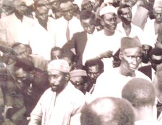 Alieu Ebrima Cham Joof - The Bread and Butter Demonstration of 1959. Cham Joof in the white hat and shirt holding a file on his hand.