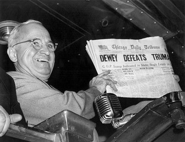 "Man in gray suit and wire glasses holding newspaper that says ""Dewey Defeats Truman"""