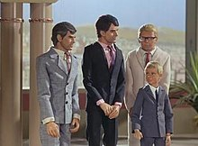 Three men and a boy stand in a palatial setting. A desert landscape is visible from a balcony in the background. One man on the far left is grey-haired and wears a grey suit and tie, the man to the right of him dark-haired and in deep navy blue. Both men are orientated in the direction of the (blond-haired) boy, who is also formally attired in grey. The third man, also blond but wearing a cream-shaded suit, stands directly behind him.